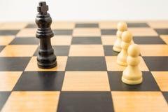 Trzy białego pionka przeciw czarnemu królewiątku zdjęcie royalty free