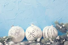 Trzy białej piłki i futerkowych drzewnych świerczyny przeciw błękit ścianie Zdjęcie Stock