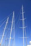Trzy bielu jachtu masztu na niebieskim niebie Fotografia Stock