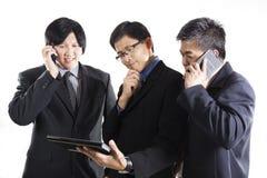 Trzy biznesmenów spotkanie i używać telefon komórkowy Zdjęcia Royalty Free