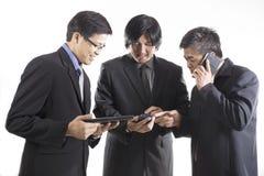 Trzy biznesmenów spotkanie i używać telefon komórkowy Zdjęcia Stock