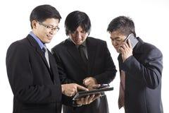 Trzy biznesmenów spotkanie i używać telefon komórkowy Fotografia Royalty Free