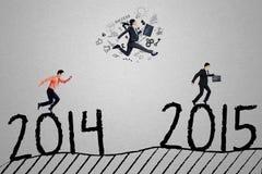 Trzy biznesmena w rasie dosięgać liczbę 2015 Zdjęcie Stock