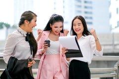 Trzy biznesowej Azjatyckiej dziewczyny postępują jak szczęśliwy i podniecający na zewnątrz biura podczas dnia czasu zdjęcie stock