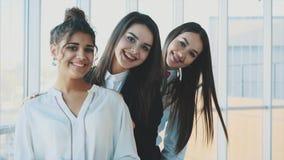 Trzy biznesowej dziewczyny opuszcza ich głowy ono uśmiecha się, demonstrujący ich wydajnego sukces w biznesie i integrację zdjęcie wideo