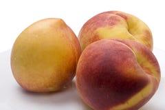 Trzy brzoskwini na talerzu, tło na czystym bielu Obraz Stock