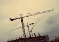 Trzy budują żurawia przeciw tłu dżdżysty szary niebo Zdjęcie Royalty Free
