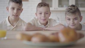 Trzy ch?opiec patrzeje talerza z smakowitymi ma?ymi kulebiakami stoi na stole w tle Ch?opiec s? g?odne Poj?cie zdjęcie wideo