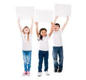 Trzy cheeerful dziecka trzyma en pustego papier ciąć na arkusze nad one zdjęcia royalty free
