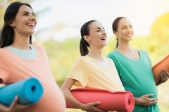 Trzy ciężarnej dziewczyny pozuje w parku z joga matują w ręce I uśmiechają się zabawę Fotografia Royalty Free
