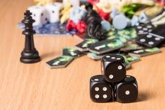 Trzy ciemnego kostka do gry na zamazanym tle szachowi kawałki i domina Zdjęcie Stock