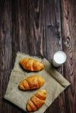 Trzy croissants z szkłem mleko na gałganianym i drewnianym stole obraz stock