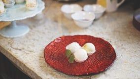 Trzy cukierki są na czerwonym szklanym talerzu z kawałkiem mennica obraz stock