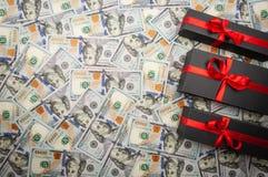 Trzy czarnego prezenta pudełka z łękiem na tle dolary Odgórny widok, kopii przestrzeń fotografia stock