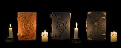 Trzy czarnej magii książki z świeczkami w ciemności Zdjęcia Stock