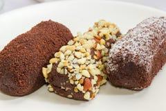 Trzy czekoladowego ciasta z różnymi kropieniami na białym dis Zdjęcie Royalty Free