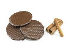 Trzy czekoladowego ciastka i cynamonowych kije odizolowywający Obrazy Royalty Free