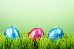 Trzy czekolady foliowego Wielkanocnego jajka na trawie Fotografia Stock