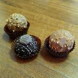 Trzy czekolady w papierowych koszach na drewnianym tle, zdjęcie royalty free