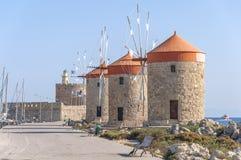 Trzy czerwieni dachowy stary wiatraczek na wybrzeżu z błękitnym chmurnym niebem latarnią morską i Fotografia Royalty Free