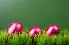 Trzy czerwieni foliowego Wielkanocnego jajka na trawie Zdjęcia Stock