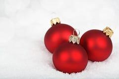 Trzy czerwonego baubles na śniegu Obrazy Royalty Free
