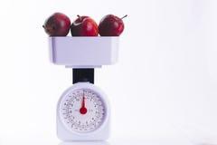 Trzy czerwonego jabłka na ważyć ważą Obraz Royalty Free