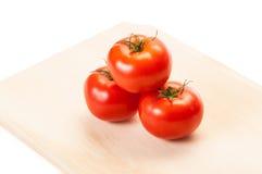 Trzy czerwonego pomidoru układającego na drewnianej desce Zdjęcia Royalty Free