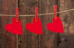 Trzy czerwonego serca wiesza na clothesline. fotografia royalty free