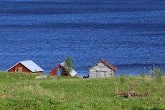 Trzy domu i idyllicznego błękitnego jezioro w Bakvattnet, Szwecja Zdjęcia Royalty Free