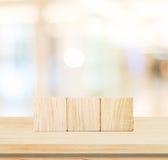 Trzy drewnianego sześcianu na stołu i plama abstrakta tle Obrazy Royalty Free