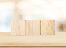Trzy drewnianego sześcianu na stołu i plama abstrakta tle Obraz Stock