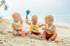 Trzy dzieci berbecia obsiadanie na tropikalnej plaży w Tajlandia i bawić się z piasek zabawkami Żółte koszula Dwa chłopiec i jede Obraz Stock