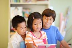 Trzy dzieci spojrzenie przy pastylka komputerem Obraz Royalty Free