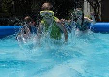 Trzy dzieciaka biega naprzód w basenie robi fala obraz stock