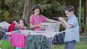 Trzy dzieciaka bierze daleko pralnię od obwieszenie linii kosz zbiory wideo