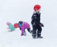 Trzy dzieciaka jest ubranym hełmy bawić się w śnieżnym skłonie obraz stock