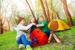 Trzy dzieciaka pakuje rzeczy w czerwonego plecaka Obrazy Royalty Free