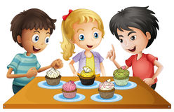 Trzy dzieciaka przy stołem z babeczkami royalty ilustracja