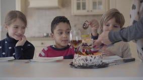 Trzy dzieciaka przy stołem z małymi torta i soku szkłami Ręka kobieta ciie tort i stawia kawałek chłopiec talerz zbiory wideo