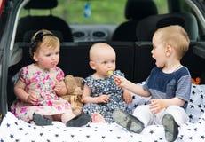 Trzy dzieciaka siedzą w samochodowym bagażu przewoźniku Zdjęcia Royalty Free