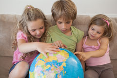 Trzy dzieciaka z kuli ziemskiej obsiadaniem w żywym pokoju Zdjęcie Stock