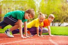 Trzy dzieciaków zakończenie w mundurach przygotowywających bieg Fotografia Royalty Free