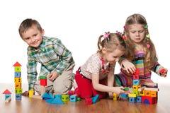 Trzy dziecka bawić się na podłoga Obraz Stock