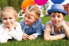 Trzy dziecka kłama na trawie z balonami obraz stock