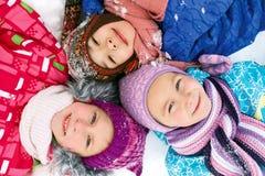 Trzy dziecka kłamają na śniegu w zimie i patrzeć upwards zdjęcia stock