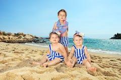 Trzy dziecka siedzi na piaskowatej plaży Obraz Royalty Free
