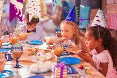 Trzy dziecka siedzi po cichu podczas gdy jedzący smakowitego jedzenie obrazy royalty free