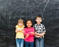 Trzy dziecka stoi pod patroszonym parasolem obrazy stock
