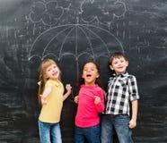 Trzy dziecka stoi pod patroszonym parasolem zdjęcie royalty free
